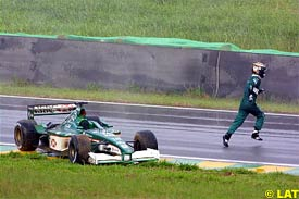 Eddie Irvine leaves his car after spinning