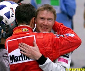 Michael Schumacher hugs Mika Hakkinen after the race