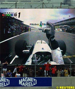 A giant TV screen shows Coulthard after stalling his car