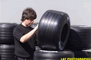 A tyre technician prepares for tomorrow's practice session