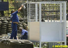 workers at Interlagos prepare special cages to protect track marshals