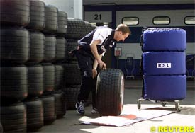 A mechanic rolls a tyre in the BMW-Williams pit