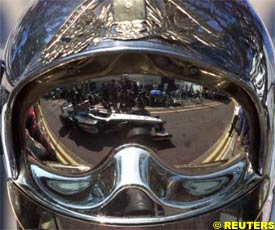 David Coulthard in his McLaren Mercedes is reflected in the helmet of a fireman